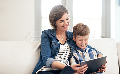 Buy stock photo Cropped shot of an attractive young woman and her son sitting on the sofa at home