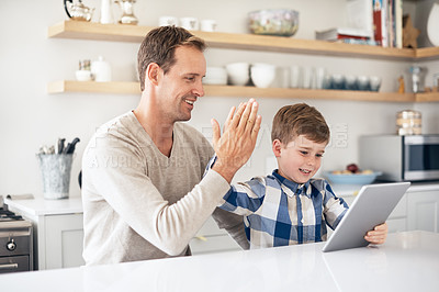 Buy stock photo Cropped shot of a handsome young man and his son high fiving while using a tablet in the kitchen