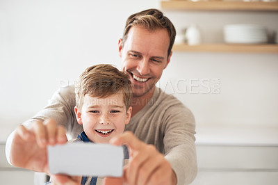 Buy stock photo Cropped shot of a handsome young man and his son taking selfies at home