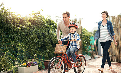 Buy stock photo Full length shot of an adorable little boy learning how to ride a bike with his parents outside