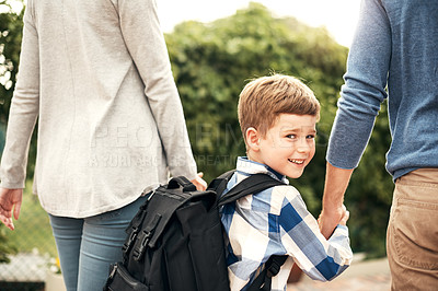 Buy stock photo Shot of a young boy carrying his backpack while walking with his parents