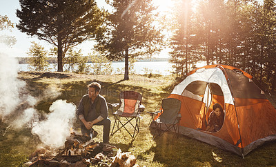 Buy stock photo Shot of a young married couple camping in the forest