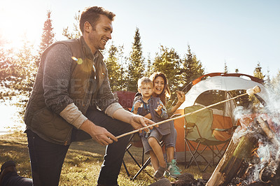 Buy stock photo Shot of a young family camping in the forest
