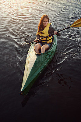 Buy stock photo High angle shot of a beautiful young woman kayaking on a lake outdoors