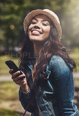 Buy stock photo Portrait of an attractive young woman using a cellphone at the park