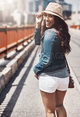 Buy stock photo Shot of a beautiful young woman looking over her shoulder while out for a walk