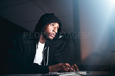 Buy stock photo Low angle shot of a young male hacker cracking a computer code in the dark