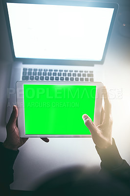 Buy stock photo High angle shot of an unrecognizable man using a tablet while working late in the office