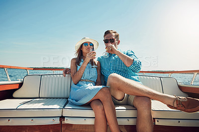 Buy stock photo Shot of a young couple having champagne on a boat ride
