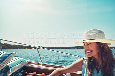 Buy stock photo Cropped shot of an attractive young woman sitting at the back of a yacht on the open seas