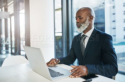 Buy stock photo Cropped shot of a mature businessman working on his laptop