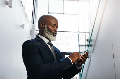 Buy stock photo Cropped shot of a mature businessman using his cellphone in an office