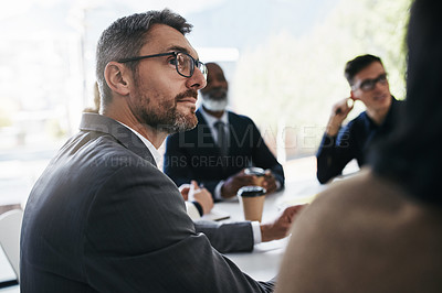 Buy stock photo Shot of a businessman having a meeting with his colleagues in an office