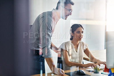 Buy stock photo Shot of two businesspeople working on a computer in an office