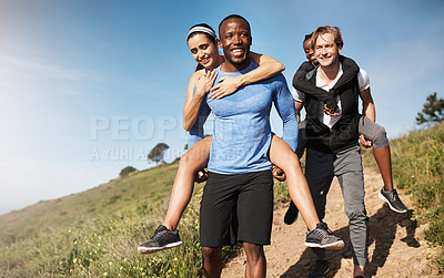 Buy stock photo Shot of two men challenging each other by carrying their girlfriends downhill