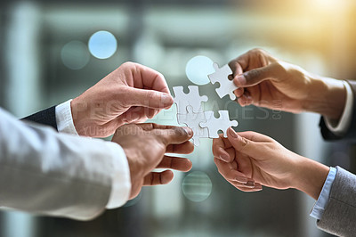 Buy stock photo Cropped shot of a group of businesspeople completing a puzzle together in a modern office