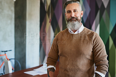 Buy stock photo Portrait of a cheerful middle aged man looking at the camera while standing alone in his office during the day