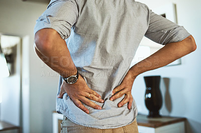 Buy stock photo Rearview shot of an unrecognizable man holding his back in discomfort due to pain inside at home