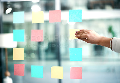 Buy stock photo Cropped shot of a businesswoman arranging sticky notes on glass in a modern office