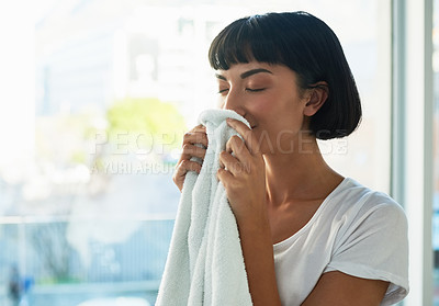 Buy stock photo Cropped shot of a young woman smelling freshly washed towels at home