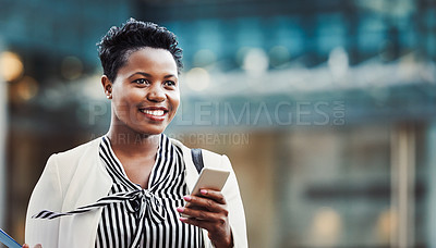 Buy stock photo Shot of a young businesswoman using a mobile phone on the go in the city