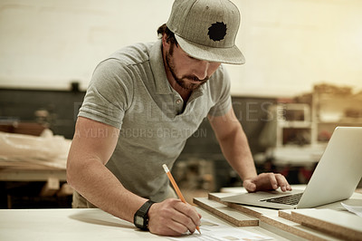 Buy stock photo Cropped shot of a handsome young carpenter writing down measurements in his workshop