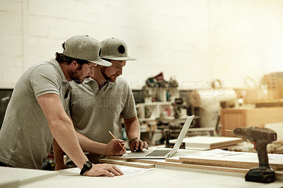 Buy stock photo Cropped shot of two handsome young carpenters taking down measurements in their workshop