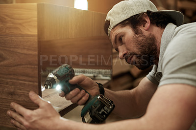 Buy stock photo Cropped shot of a handsome young carpenter putting together a wood piece in his workshop