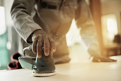 Buy stock photo Cropped shot of an unrecognizable male carpenter sanding down one of his wood pieces in the workshop