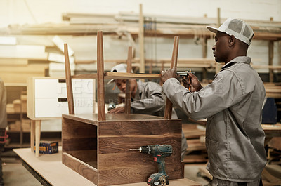 Buy stock photo Cropped shot of two young male carpenters putting together a wood piece in their workshop