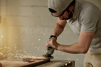 Buy stock photo Cropped shot of a handsome male carpenter using an angle grinder in his workshop