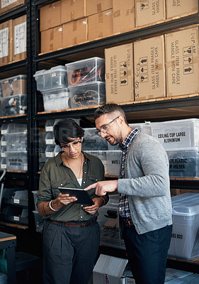 Buy stock photo Shot of a man and woman using a digital tablet together in a workshop