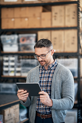 Buy stock photo Shot of a man using a digital tablet in a workshop