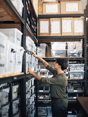 Buy stock photo Shot of a woman looking through the shelves in a workshop