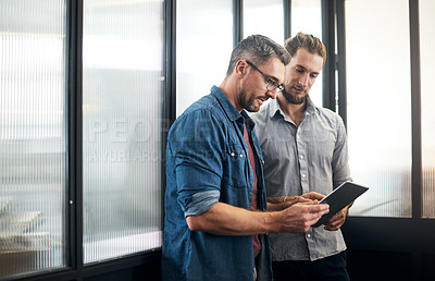 Buy stock photo Shot of two designers working together on a digital tablet in an office
