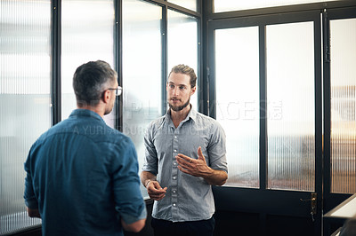 Buy stock photo Shot of two designers having a discussion in an office