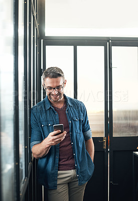 Buy stock photo Shot of a mature designer using a cellphone in an office