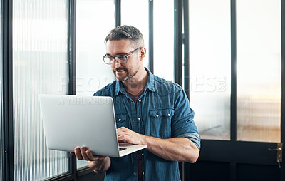 Buy stock photo Shot of a mature designer using a laptop in an office