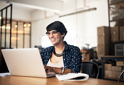 Buy stock photo Shot of a young woman using a laptop in a workshop