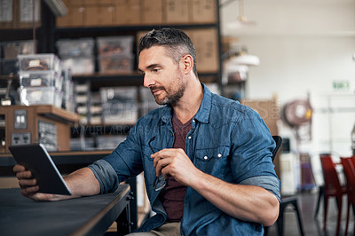 Buy stock photo Shot of a mature man using a digital tablet in a workshop