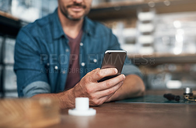 Buy stock photo Closeup shot of an unrecognizable designer using a cellphone in an office