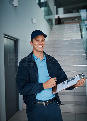 Buy stock photo Cropped shot of a handsome young man marking off his checklist on a clipboard indoors