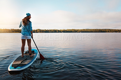 Buy stock photo Shot of a young woman paddle boarding on a lake