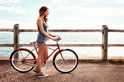 Buy stock photo Shot of a beautiful young woman with her bicycle on the promenade