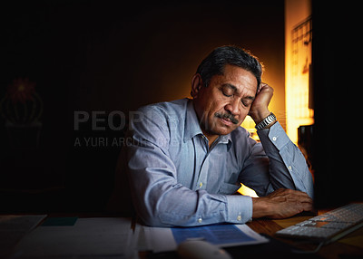 Buy stock photo Shot of a mature businessman sleeping at his desk while working late in an office
