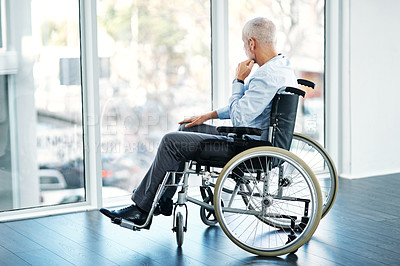 Buy stock photo Shot of a mature man sitting in a wheelchair and looking out the window