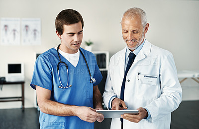 Buy stock photo Shot of two medical practitioners using a digital tablet in a hospital