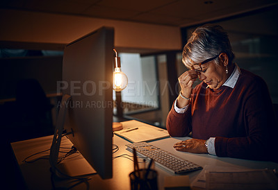 Buy stock photo Shot of a mature businesswoman looking stressed out while working late in an office