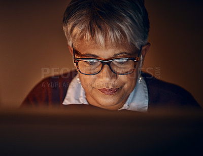 Buy stock photo Shot of a mature businesswoman working late in an office