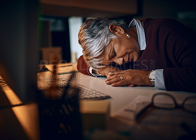 Buy stock photo Shot of a mature businesswoman sleeping at her desk while working late in an office